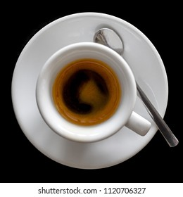 Small italian espresso in white ceramic cup with spoon isolated on black from above.