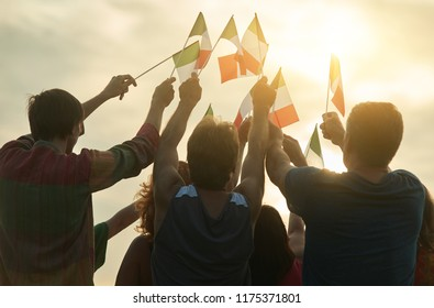 Small italian flags against sunshine background. Bright evening sky at the down.