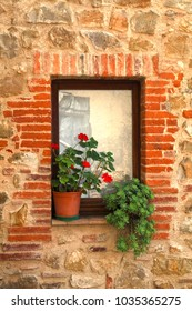 Small italian window with nice red geranium flower in old stone house, Tuscany, Italy