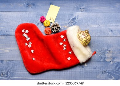Small items stocking stuffers or fillers little christmas gifts. Christmas sock toned wood background top view. Fill sock with gifts or presents. Celebrate christmas. Contents of christmas stocking.