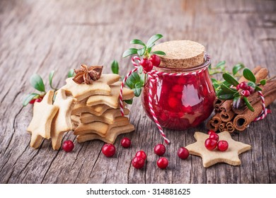 A small jar of homemade fresh spicy sweet cranberry sauce with cinnamon next to a stack of homemade gingerbread cookies in the shape of stars on a dark wooden background. selective Focus