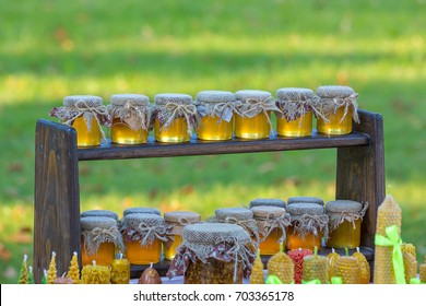 Small jars of honey are on a wooden shelf, Honey sold at the fair of honey. Beautiful evening light.