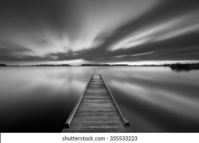 A small jetty on a lake near Amsterdam The Netherlands in black and white. A slow shutter speed was used to see the movement of the clouds in the sky. Photographed at dawn.