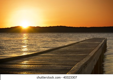 A small jetty sticks out onto the lake at sunrise
