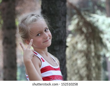 small joyful girl shows fingers a victory