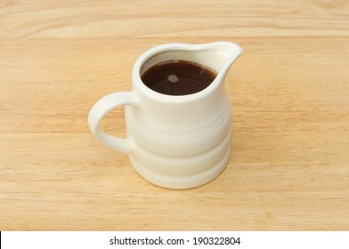 Small jug of gravy on a wooden board