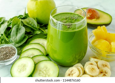 Small juice glass filled with green kale and spinach smoothie surrounded by ingredients sitting on kitchen counter