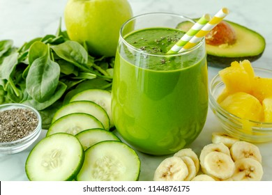 Small juice glass filled with green kale and spinach smoothie with green and yellow swirl straws surrounded by ingredients