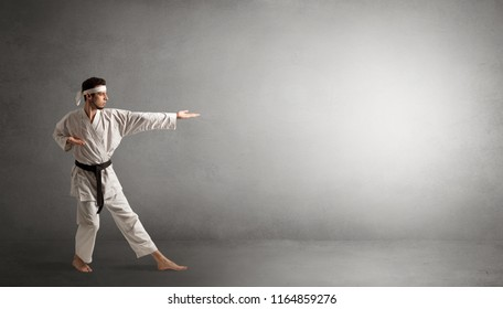 Small karate man fighting in an empty grey copy space