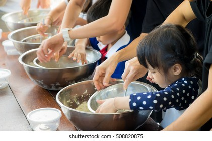 Small kid and family is learning how to make ice cream in a cooking class. Parent are helping children in Baking sweet bakery in a cooking group club activity.