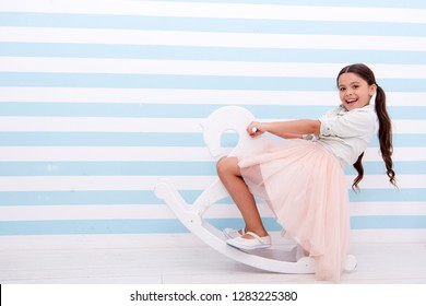 small kid fashion. International childrens day. Childhood happiness. small girl child with perfect hair. Happy little girl. Beauty and fashion. playful girl on toy pony. Loving her new style.