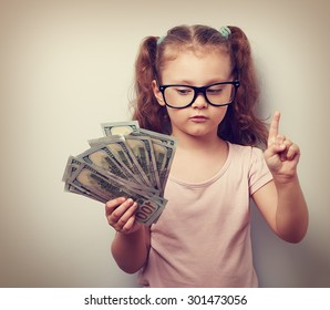 Small kid girl holding dollars and have an plan how earning much money in crisis. Serious child showing finger. Vintage closeup portrait