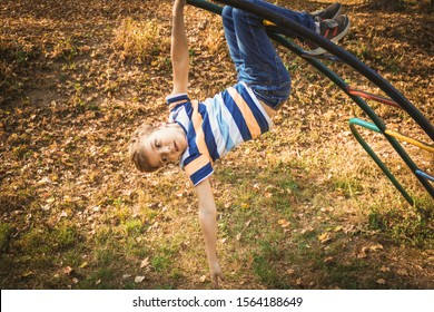 Small kid handing on monkey bars while playing outdoors at the playground.