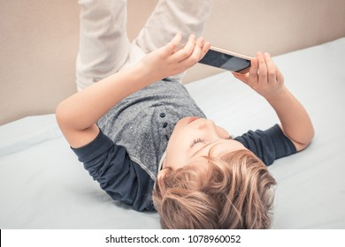 Small kid having fun and taking selfie with cell phone while lying on the bed.