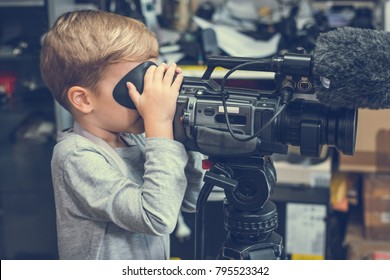 Small kid using video camera while filming in movie studio.