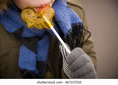 Small kid in warm clothes and nice blue scarf with a big yellow lollipop. Easter celebration. Child eating a candy in shape of a cockerel. Russian candy on a stick. Winter carnival.