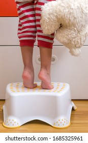 Small kids legs and feet tippy-toes on a step stool to reach for something on a cabinet counter.