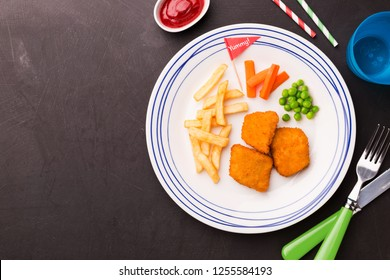 Small kid's meal - chicken nuggets, chips, carrot and green peas. Colorful dinner on black chalkboard background. Plate captured from above (top view, flat lay). Layout with free copy (text) space.