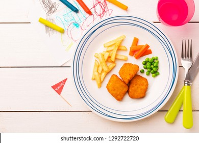 Small kid's meal - chicken nuggets, french fries, carrot and green peas. Colorful dinner on white wooden table. Plate captured from above (top view, flat lay). Layout with free copy (text) space.
