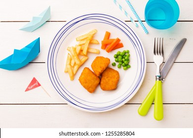Small kid's meal - fish, chips, carrot and green peas. Colorful dinner on white wooden table. Plate captured from above (top view, flat lay).