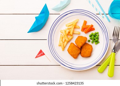 Small kid's meal - fish, chips, carrot and green peas. Colorful dinner on white wooden table. Plate captured from above (top view, flat lay). Layout with free copy (text) space.