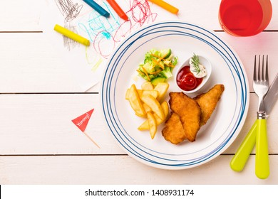 Small kid's meal - fried chicken strips, french fries, salad and ketchup. Colorful dinner on white wooden table. Plate captured from above (top view, flat lay). Layout with free copy (text) space.