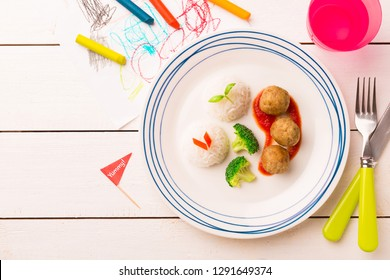 Small kid's meal - meatballs, rice and broccoli. Colorful dinner on white wooden table. Plate captured from above (top view, flat lay). Layout with free copy (text) space.