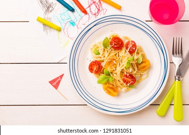 Small kid's meal - spaghetti with cherry tomatoes and basil. Colorful italian dinner on white wooden table. Plate captured from above (top view, flat lay). Layout with free copy (text) space.