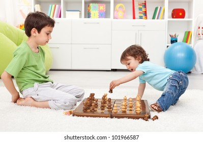 Small kids playing chess in their room