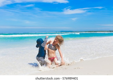 small kids playing together outdoors on cloudy summer day, ocean coastline with white sand and shallow wavy water, siblings sitting, jumping and running after each other