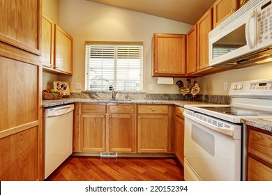 Small kitchen area with granite tops and white appliances