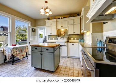 Small kitchen interior with white wooden cabinets, tile floor and kitchen island