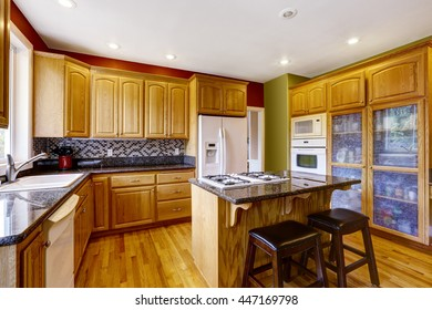 Small kitchen with island, dark granite counter top, also red walls and hardwood floor
