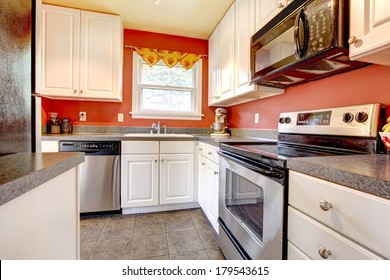 Small kitchen room with concrete tile floor, red walls, steel appliances and white wooden cabinets