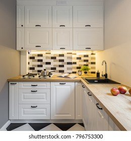 Small kitchen with white cabinet, led light and decorative tiles