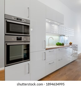 Small kitchen with white cupboards and drawers, wooden floor and silver oven and microwave