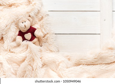Small knitted baby toy bear is covered with a warm blanket, flat lay, top view