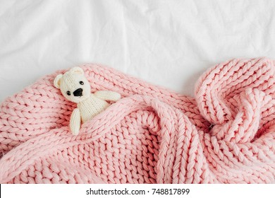 A small knitted baby toy-bear is covered with a warm blanket, flat lay,  top view