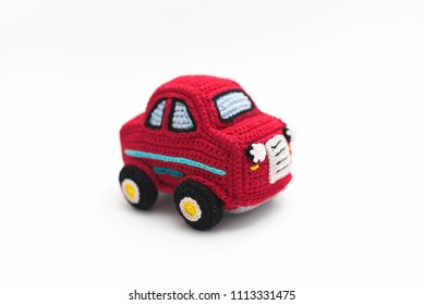 small knitted red baby machine on white background