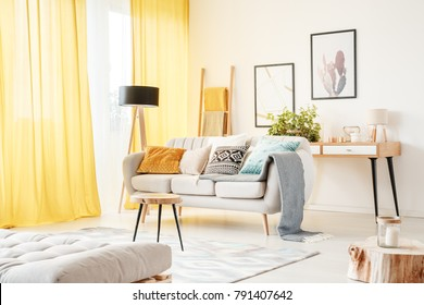 Small ladder standing behind a comfy couch in a bright boho apartment interior with yellow curtains