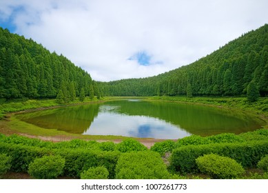 Small lake called Lagoa das Empadadas in Portuguese, surrounded by green forest, located on Sao Miguel island of Azores, Portugal.