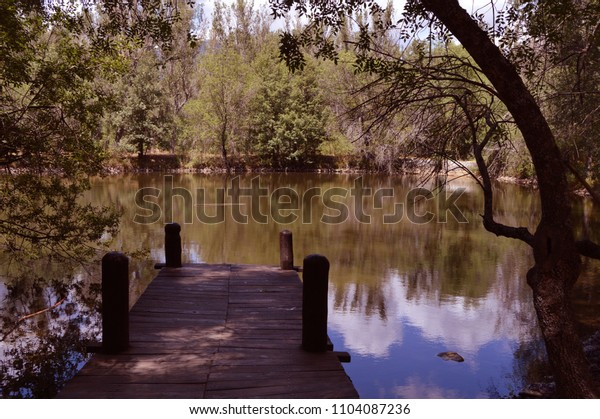 Small lake with jetty in the Finnish forest in Rascafría province of Madrid. Spain.