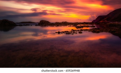 Small lake in the ocean. Ocean View with big mountains in the background. Foreground with a natural ocean pool. Middleground with rocks and sunset reflexion