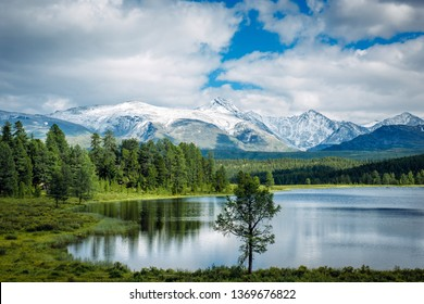 Small lake on grass and fluffy clouds over green meadows and snowy peaks. Highland lake, Altay, Siberia.