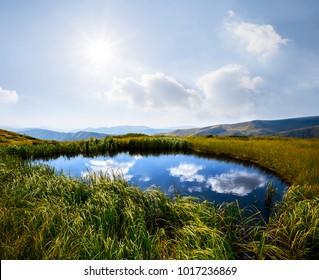 small lake on a mountain plateau under a sparkle sun