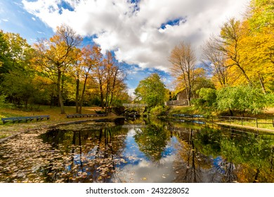 Small Lake with reflection of trees in water, in a Park of Montreal in Autumn and Little Bridge in Background