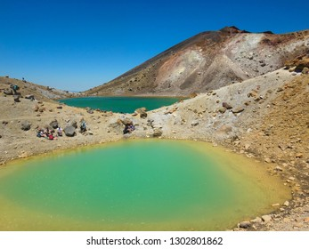 small lake with turquoise water surface, viewed from popular hiking trail Tongariro Alpine Crossing, famous one day hike trip in volcanic landscape and mountains with lookd of Mordor, New Zealand
