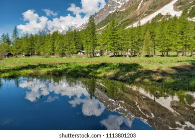 small lake in Val Ferret with trees mountains and clouds reflected in the water in spring season
