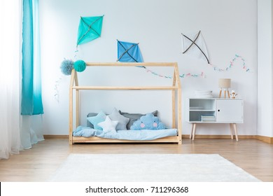 Small lamp on cupboard next to bed with star shaped pillows on blue bedding in boys bedroom with DIY kites on white wall