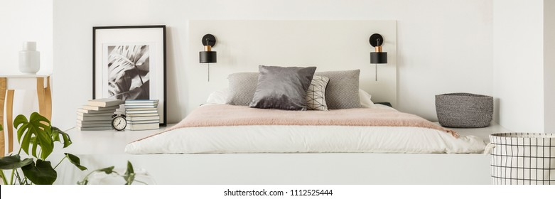 Small lamps placed on white bedhead by the simple mattress bed with pillows in bedroom interior with books, clock and poster